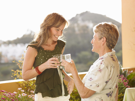 Senior woman and adult daughter making celebratory toast on balcony Stock Photo