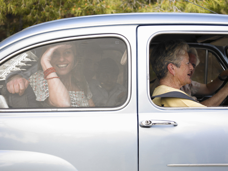 Multi-generational family sitting in car, side view, smiling