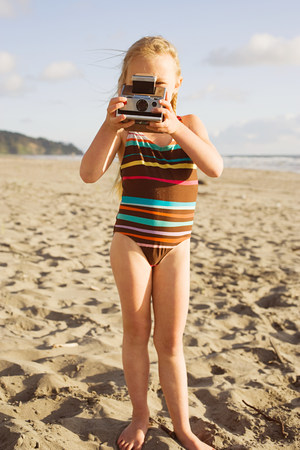 A girl using an instant camera on the beach