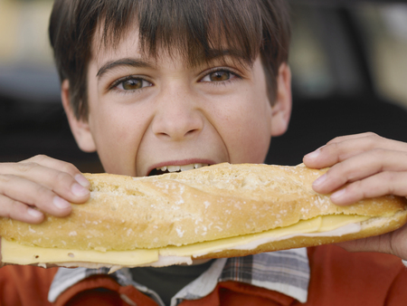 Boy (8-10) eating large cheese baguette, close-up, portrait