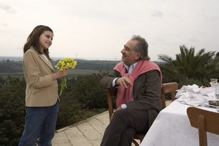 Girl (9-11) giving flowers to grandfather at a table outside