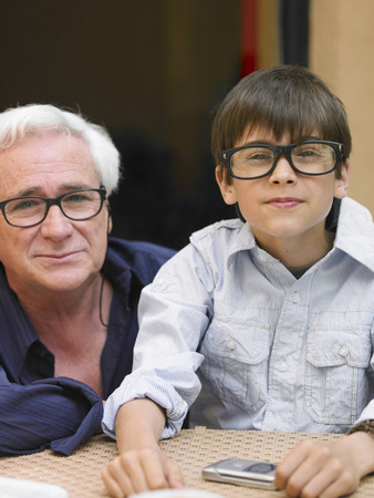 Boy (8-10) and grandfather sitting at café table, wearing black-rimmed spectacles