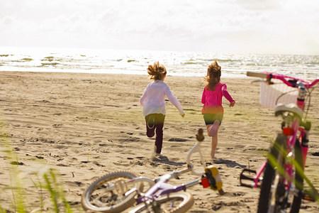Girls running toward sea at beach Stock Photo