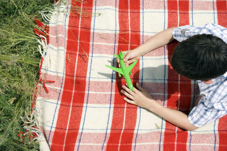 Boy playing with green toy plane Stock Photo