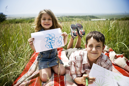 Two children showing their drawings