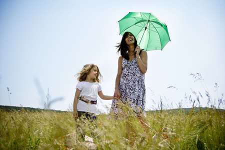 Woman with daughter holding umbrella  Imagens