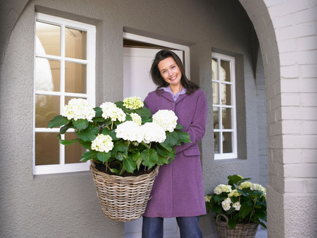 Woman holding flowers on the patio Imagens