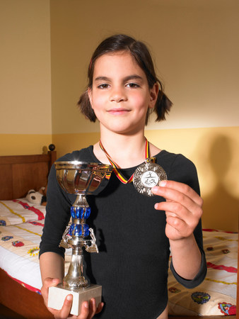 Girl holding a trophy and a medal