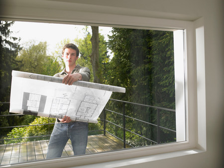 Man with blueprint, outdoors Imagens