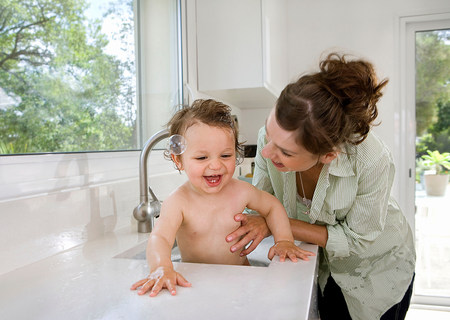 Mother with baby in kitchen sink