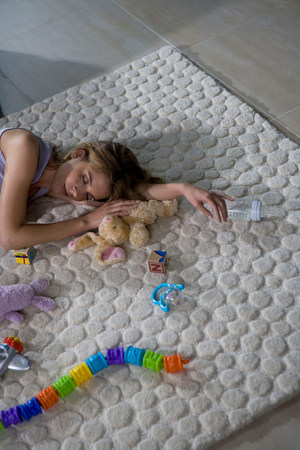 Young mother sleeping on carpet