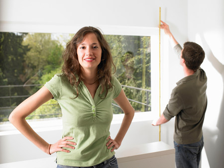 Couple taking measurement of their home Stock Photo
