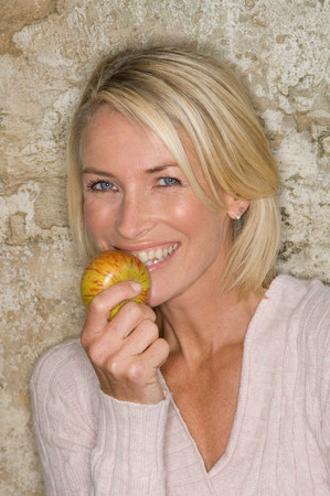 Smiling woman eating apple