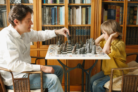 Father playing chess with young boy Imagens