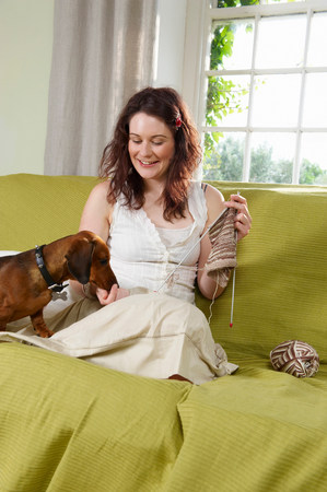 Young woman on couch with dog Stock Photo