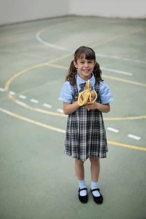 School girl holding skipping rope Stock Photo
