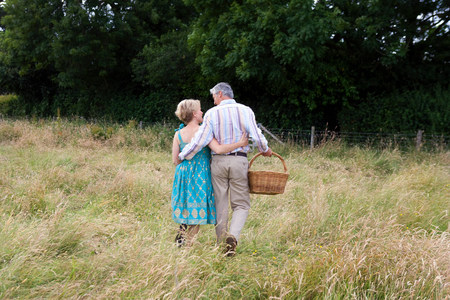 Couple waking towards  gate in a field Stock Photo