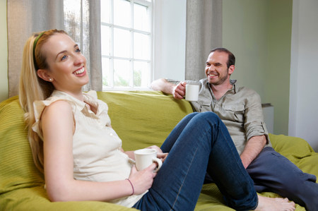 Couple sitting on couch, with mugs