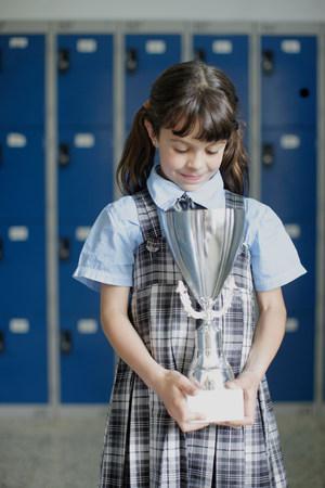 School girl looking down at trophy