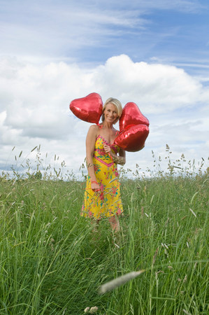 Smiling woman in field with balloons Stock Photo