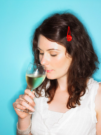 Young woman sniffing white wine