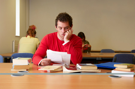 Bored young man seated at desk studying