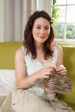 Young woman knitting on couch Stock Photo