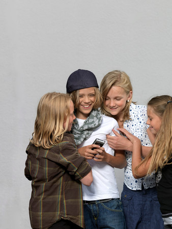 Four kids with mobile phone Stock Photo