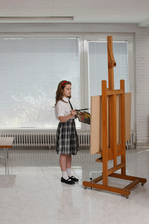 Young girl painting on easel Imagens