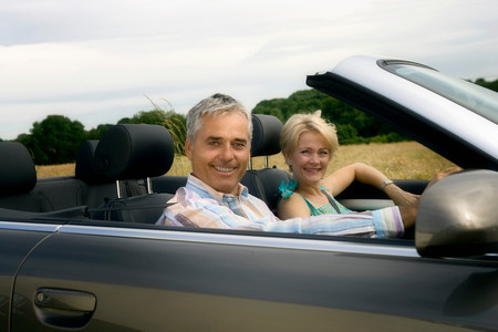 Middle age couple in convertible car Banco de Imagens