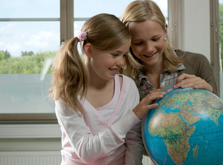 Two girls with earth globe Stock Photo