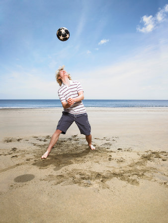 Young man with football on beach