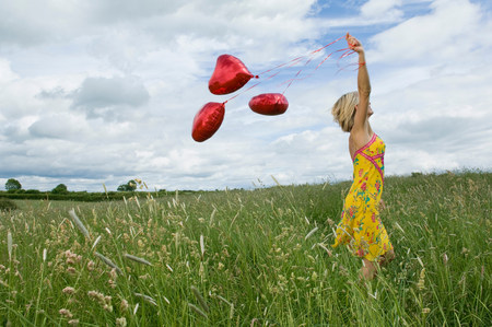 Woman walking with balloons in field Stock Photo