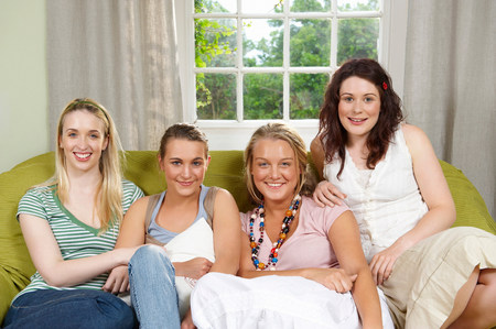 Four young women seated on couch Stock Photo - 113870713