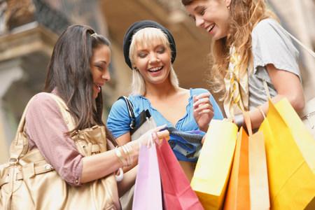 Young women walking with shopping bags Stock Photo