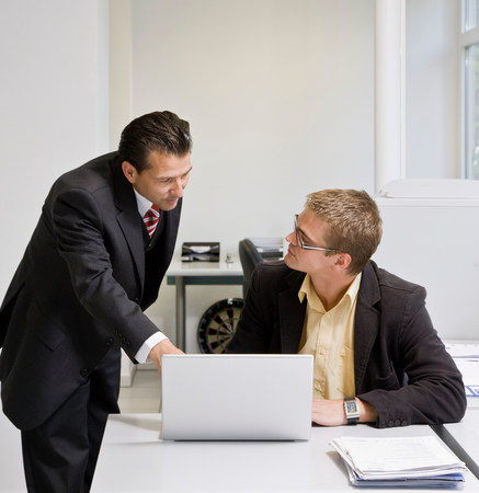 Boss looking at laptop with co-worker Stock Photo