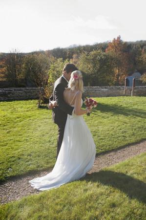 A wedding couple walking along a path