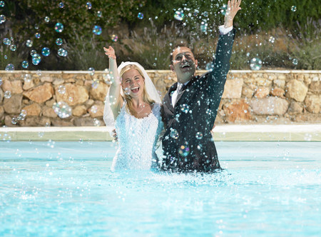 Bride and groom splashing in pool Banco de Imagens - 113871132