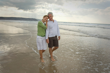 Couple walking on a beach Stock Photo
