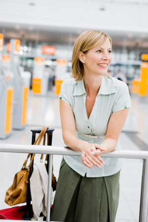 Woman leaning on rail waiting Stock Photo