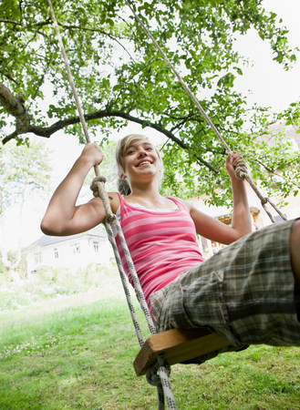 Young girl on a tree swing