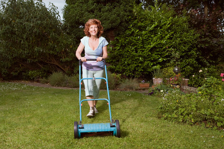 Mature woman mowing lawn