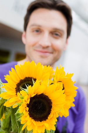 Man giving flowers to the viewer Stock Photo