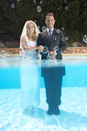 Bride and groom in pool with bubbles Banco de Imagens - 113872518