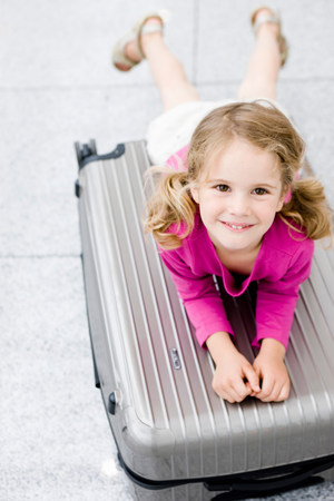 Girl smiling leaning on suitcase Stock Photo