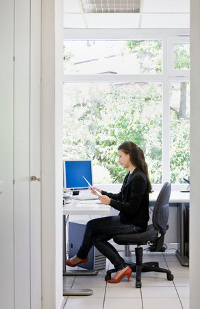 Woman at desk in office Imagens