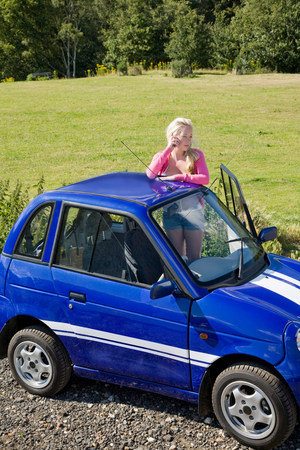 Young woman on phone by electric car