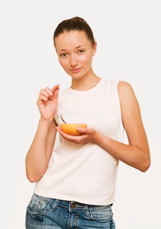 Girl eating a pink grapefruit