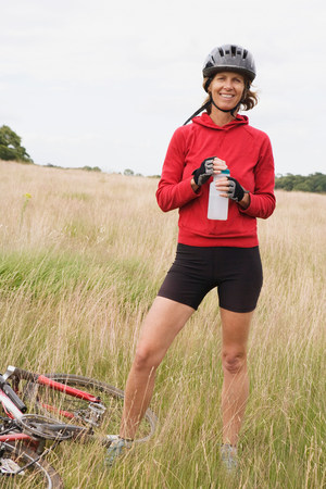 Woman cyclist holding water bottle 版權商用圖片