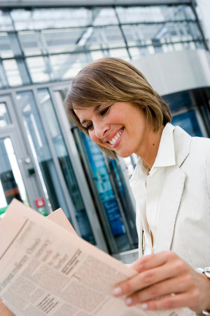 Woman reading newspaper smiling Stock Photo